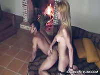 Shemale in business clothes strips by the fire and fucks her hunky stud
